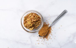 Top view of mustard sauce and mustard seeds in a spoon on a marble background with copy space