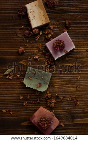 Top view of natural bar soaps with dry roses on wooden background.