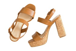 Top view of new pair of stylish brown high heels with cork soles, beautiful shoes for ladies on white wooden background