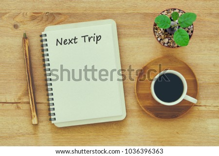 Top view of  NEXT TRIP message on notebook with pencil ,coffee cup and Cactus in flowers in a pot on wooden table. - Shutterstock ID 1036396363