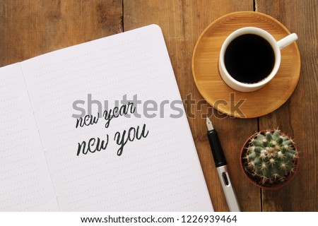 Top view of notebook and text NEW YEAR NEW YOU, cup of coffee over wooden desk #1226939464