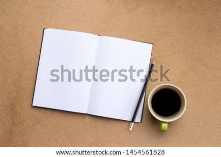 Top view of notebook,pencil and cup of coffee on wood table background.Business desk minimal style concept with copy space for any design.Take note of the product for book with paper. #1454561828