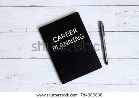 Top view of notebook written with CAREER PLANNING with pen on white wooden background.