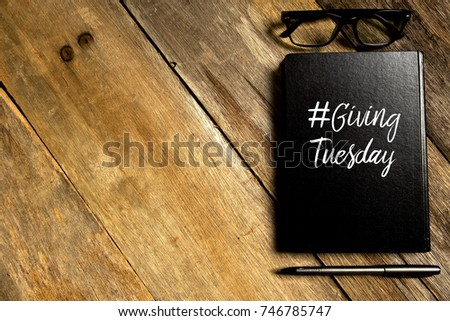 Top view of notebook written with hashtag GIVING TUESDAY with pen and glasses on wooden background with copy space.Flat lay. #746785747