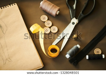 Top view of notepad with fashion sketch, scissors, folded measuring tape, zip, buttons, spools and thimble on workplace of tailor