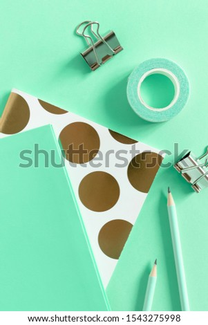 Top view of notepads, pencils, duct tape, paper clips on mint background