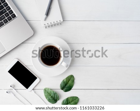 top view of office desk table with coffee cup, notebook, laptop, plastic plant, smartphone and keyboard on white background, graphic designer, Creative Designer concept. #1161033226