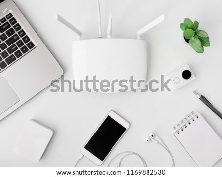 top view of office desk table with notebook, plastic plant, laptop, smartphone  and modem router on white background, internet and network concepts.