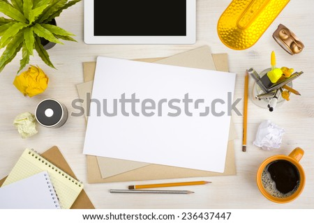 Top view of office desk with paper, stationery and tablet computer
