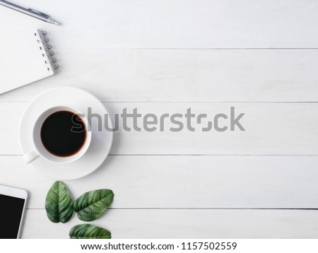 top view of office desk workspace with coffee cup, notebook, plastic plant and smartphone on white background, graphic designer, Creative Designer concept. #1157502559