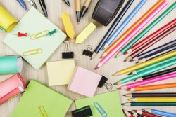 Top view of office desktop with colorful supplies and other items. Workplace concept