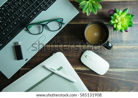 Top view of office stuff graphic design with pen mouse pad laptop wireless mouse and coffee cup on wooden table.Concept graphic design workplace #585131908