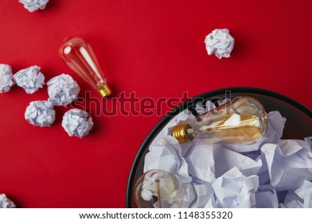 top view of office trash can with crumpled papers and vintage incandescent lamps on red tabletop