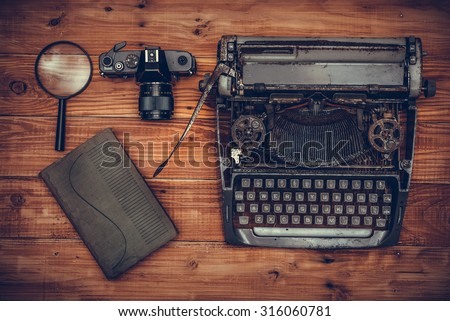 Top view of old typewriter, old camera, magnifying glass and book on wooden background #316060781