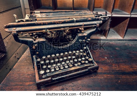 Top view of old typewriter on wooden table. Warm effect and color-toning applied.  #439475212