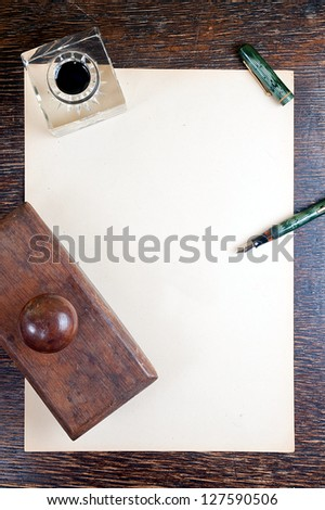 top view of old yellowed sheet of paper at wooden vintage desk. fountain pen, inkstand with black ink and blotting paper.