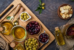 Top view of olives and olive oil bottles on table in a rustic kitchen