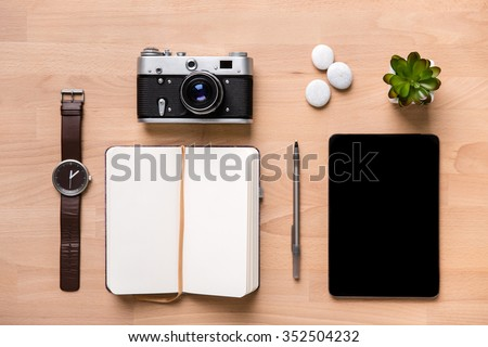 Top view of opened blank notepad, pen, watch, vintage camera, tablet and flower on wooden background
