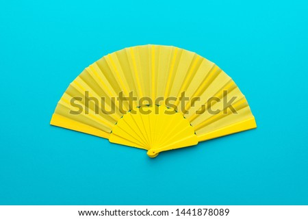 Top view of opened yellow fan mockup over blue turquoise background. Minimalist flat lay photo of folding fan with central composition.