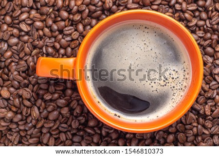 Top view of orange cup of black coffe put it on coffe beans background #1546810373