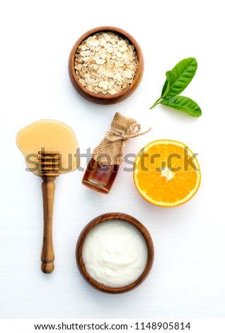 top view of orange oats yogurt and honey on white wooden background.Best and easiest for DIY facial masks.Homemade spa product for acne scar face,body scrub for radiant and glow skin. Recipe of cakes.
