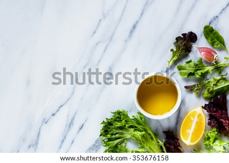Photo of Top view of organic green lettuce with olive oil, lemon and garlic on marble texture. Background layout with free text space. Healthy food, cooking concept.