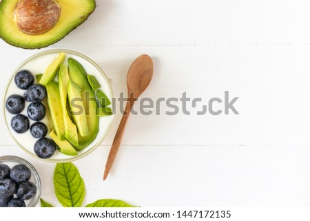 Top view of organic yogurt topped with avocado and blueberry on white wooden background, healthy and nutritious diet