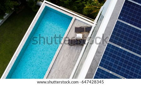 Top view of outdoor swimming pool and solar panels on the roof of villa #647428345