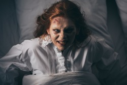 top view of paranormal girl in nightgown lying in bed