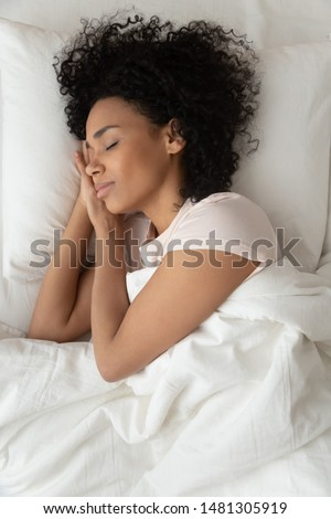 Top view of peaceful african American young woman lying in comfortable bed sleeping on white sheets, calm biracial black millennial girl relaxing napping in cozy bedroom seeing dreams or daydreaming