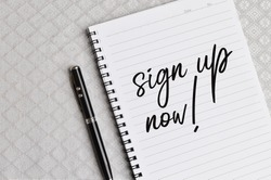 Top view of pen and notebook written with text SIGN UP NOW!. Business and education concept.