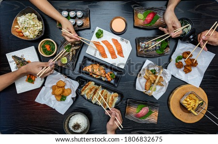 Top view of people eating Japan food on wood table together.
