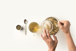 top view of person pouring fresh organic herbal tea from kettle into glass on white