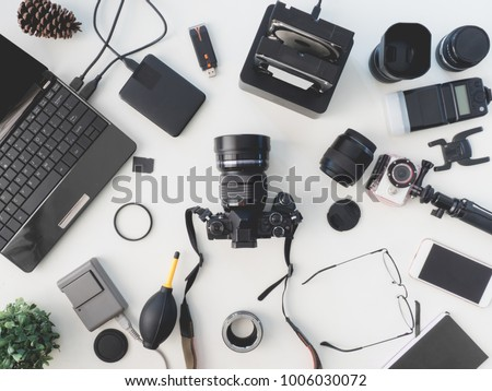 top view of photographer concept with digital camera, battery charger camera, memory card storage box, external harddisk, flash, computer laptop, notebook and camera accessory on white background.  stock photo