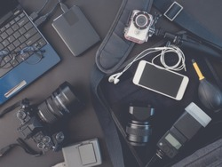 top view of photographer concept with digital camera, battery charger, memory card, external harddisk, flash, laptop and camera accessory on black background.