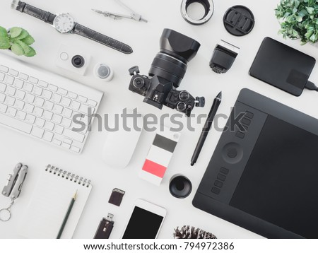 top view of photographer concept  with digital camera, memory card, smartphone, graphic tablet, external harddisk, pantone book and keyboard on white background