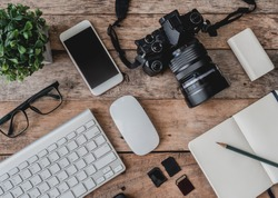 top view of photographer work station, work space concept with digital camera, notebook, memory card, smartphone on wooden table