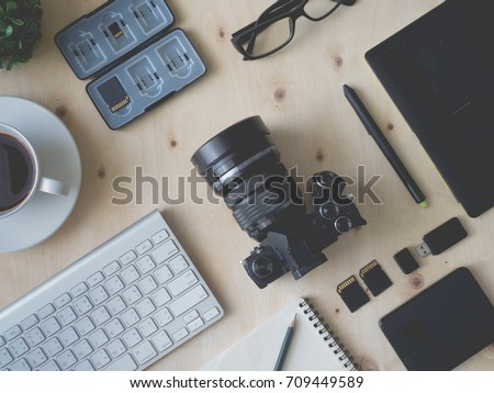 top view of photographer work station, work space concept with digital camera, notebook, memory card, smartphone, coffee cup, graphic tablet, external harddisk.