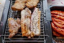 Top view of piece of barbecue pork belly and grilled steak on Electric Grill Griddle surrounded with raw meat on side.