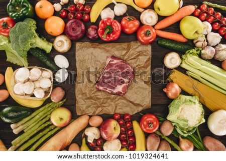 top view of piece of raw meat between vegetables and fruits on wooden table #1019324641