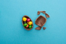 Top view of pieces and half of chocolate Easter egg with colorful candies on blue background
