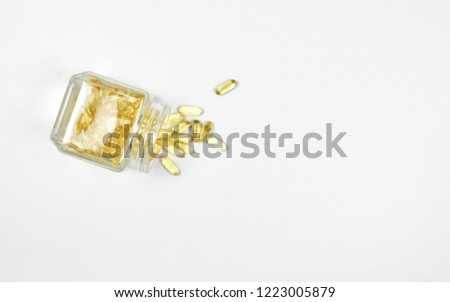 Top view of Pile overflow of fish oil capsules isolated in a glass bottle on white background. Omega 3. Vitamin E. Supplementary food background. Salmon capsules view. Copy space.
