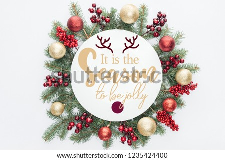 "top view of pine tree wreath with Christmas decorations with ""it is the season to be jolly"" inspiration in middle isolated on white #1235424400"