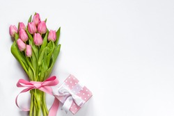 Top view of pink tulips bouquet, wrapped with pink ribbon and pink dotted gift box over white background. Copy space.