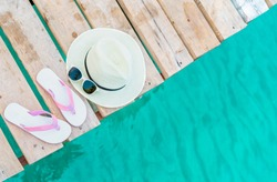 Top view of pink-white sandals, straw hat and sunglasses on wooden bridge over emerald green sea water. Summer vacation travel background. Summer vibes. Coconut tree shadow in sunglasses.