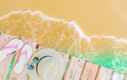 Top view of pink-white sandals, straw hat and sunglasses on wooden bridge over emerald-green sea water and golden sand beach. Summer vacation travel. Summer vibes. Coconut tree shadow in sunglasses.