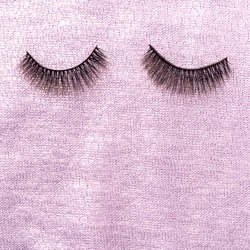 Top view of pink woolen fabric texture. Handmade piece of clothes and false eyelashes. Pattern of high-quality pink fabric material background, copy space. Handiwork concept