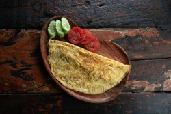 Top view of plain egg omelette with tomato and cucumber isolated on wooden background