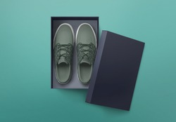 Top view of plain shoe box mockup on green background. Green pair of shoes inside shoe box.