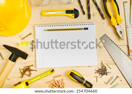 Top View of Planning a Project in Carpentry and Woodwork Industry Concept, Notebook and Assorted Woodwork and Carpentry Tools on Pinewood Workshop Table.